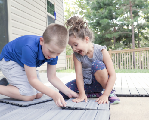Kids installing NewTechWood deck tiles.